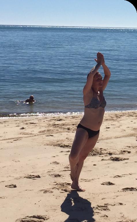 Woman doing tree pose near the sea